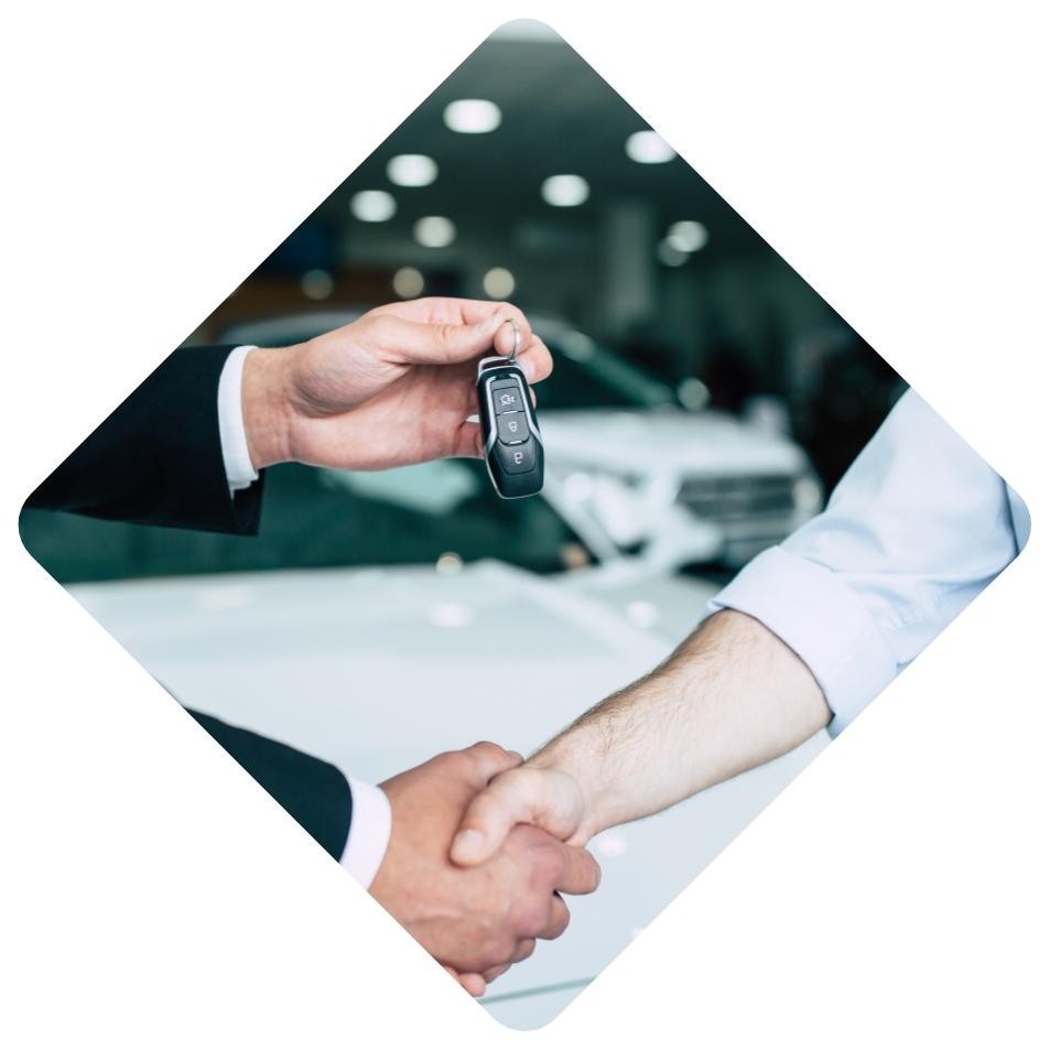 Ein Mann im Anzug übergibt einem anderen Mann händeschüttelnd einen Autoschlüssel.